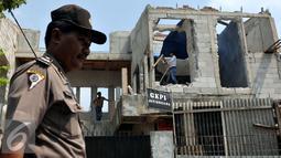 Petugas kepolisian berjaga di depan Gereja Kristen Protestan (GKPI) saat pembongkaran di Jatinegara, Jakarta Timur, Sabtu (25/7/2015). Gereja ini terpaksa dibongkar karena tidak mempunyai Ijin Mendirikan Bangunan (IMB). (Liputan6.com/Johan Tallo)
