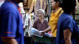 Seorang wanita lansia menjual topi mandi  di sebuah gang, yang terkenal dengan pedagang kaki lima dan pakaian, di pusat Bangkok, Thailand (8/11/2019). (AP Photo/Aijaz Rahi)