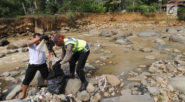 Dua Anggota Polantas Polres Bogor memungut sampah saat kegiatan aksi bersih sungai di kawasan aliran Sungai Ciliwung, gadog, Bogor (20/9). Aksi bersih sungai dalam rangka HUT lalu lintas ke-63. (Merdeka.com/Arie Basuki)