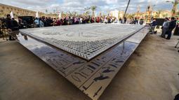 Orang-orang berkumpul di sekitar mosaik topeng Firaun Tutankhamun yang terbuat dari cangkir kopi di halaman Museum Grand Mesir di Giza, 28 Desember 2019. Mereka bergabung lebih dari 12 jam mengubah warna kopi dengan memasukkan susu dengan jumlah yang berbeda. (Mohamed el-Shahed/AFP)
