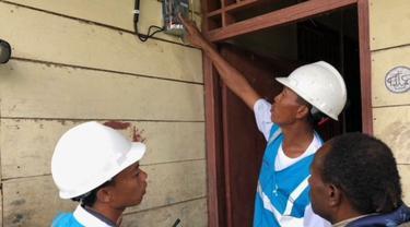Petugas PLN memasang listrik di rumah warga di Desa Parauto, Nabire, Papua. (Vina A. Muliana/Liputan6.com)