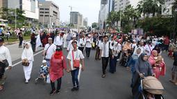 Peserta Reuni 212 beraktivitas saat Car Free Day (CFD) di kawasan Jakarta, Minggu (2/12). Momen Reuni 212 yang digelar di Monas ikut dimanfaatkan para peserta untuk menikmati Car Free Day dari Bundaran HI-Sudirman. (Liputan6.com/Angga Yuniar)
