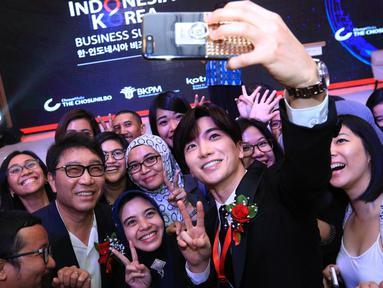 Salah satu personel Super Junior, Leeteuk berselfie bersama peserta saat menghadiri acara Indonesia-Korea Business Summit 2017 di Hotel Shangri-La, Jakarta, Selasa (14/3). (Liputan6.com/Herman Zakharia)