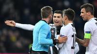 Pemain Juventus melakukan protes kepada wasit  pada laga lanjutan Liga Champions yang berlangsung di stadion Stade de Suisse, Swiss, Kamis (13/12). Juventus kalah 1-2 atas Young Boys. (AFP/Fabrice Coffrini)