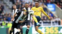 Striker Arsenal, Pierre-Emerick Aubameyang, berebut bola dengan pemain Newcastle United, Javier Manquillo, pada laga Premier League 2019 di Stadion St James' Park, Minggu (11/8). Arsenal menang 1-0 atas Newcastle United. (AP/Owen Humphreys)