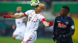 Pemain Bayern, Arjen Robben berusaha mengontrol bola dari kejaran pemian Paderborn, Adjei Antwi pada laga Piala DFB Pokal di Benteler-Arena, Paderborn, (6/2/2018). Bayern menang telak 6-0. (AFP/Patrik Stollarz)