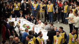 Paus Fransiskus berbincang saat menggelar jamuan makan siang di Aula Paul VI, Vatikan, Minggu (17/11/2019). Paus Fransiskus mengundang sekitar 1.500 orang miskin, tunawisma, imigran dan pengangguran untuk makan siang dalam memperingati Hari Orang Miskin Sedunia. (AP/Alessandra Tarantino)