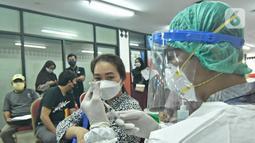 Petugas medis menyiapkan vaksin Covid-19 di Gelanggang Olahraga (GOR) Ciracas, Jakarta Timur, Kamis (24/6/2021).  Pelaksanaan vaksinasi dimulai Kamis, 24 Juni 2021 dengan target 1000 vaksin per hari. (Liputan6.com/Herman Zakharia)