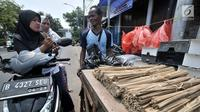 Penjual arang, tusuk sate, dan kotak pemanggang melayani pembeli di kawasan Manggarai, Jakarta, Rabu (22/8). Perlengkapan membuat sate dijual mulai dari Rp 5.000 hingga Rp 120.000. (Merdeka.com/Iqbal Nugroho)