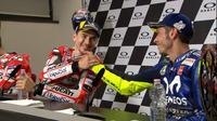 Valentino Rossi dan Jorge Lorenzo saling berjabat tangan pada sesi konferensi pers MotoGP Italia, Minggu (3/6/2018). (Twitter/MotoGP)