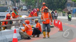 Sejumlah petugas Suku Dinas Pekerjaan Umum  melakukan peremajaan dengan melakukan pengecatan besi pembatas Fly Over di kawasan Cakung, Jakarta,  Rabu (1/4/2015). Panjang pembatas mencapai 120 meter (Liputan6.com/Yoppy Renato)
