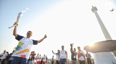 Gubernur DKI Jakarta Anies Baswedan mengangkat obor saat puncak Kirab Obor Asian Games 2018 di Jakarta, Sabtu (18/8). Obor diarak mulai dari Monumen Nasional (Monas) menuju Stadion Utama Gelora Bung Karno (GBK). (Liputan6.com/Faizal Fanani)