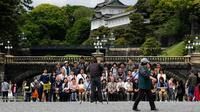 Wisatawan foto bersama di area Taman Istana Kekaisaran di Tokyo, Jepang (29/4/2019). Kaisar Jepang Akihito akan turun dari Tahta Krisan pada 30 April 2019 mengakhiri 30 tahun masa pemerintahannya. (Kazuhiro NOGI / AFP)
