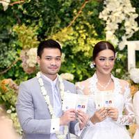 Pasangan serasi ini menunjukkan buku nikah yang menandakan mereka telah resmi menjadi pasangan suami istri. Tak hanya keduanya, keluarga serta para tamu undangan pun turut merasakan kebahagiaan dari pernikahan ini. (Andy Masela/Bintang.com)