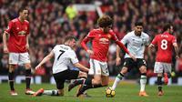 Gelandang Manchester United, Marouane Fellaini dijatuhkan gelandang Liverpool, James Milner pada laga Premier League di Stadion Old Trafford, Manchester, Sabtu (10/3/2018). MU menang 2-1 atas Liverpool. (AFP/Oli Scarff)