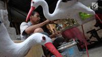 Pengrajin membuat patung di Jakarta, Jumat (16/3). Pemerintah berencana menurunkan tarif pajak penghasilan atas penjualan dibawah Rp4,8 miliar yang dikenakan tarif PP 46 sebesar 1% per bulan dari jumlah omzet, menjadi 0,5%. (Liputan6.com/Angga Yuniar)