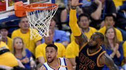 Stephen Curry (30) berusaha memasukan bola dari kawalan LeBron James (23) di gim pertama Final NBA 2017 melawan Cleveland Cavaliers di Oracle Arena di Oakland, California (1/6). Warriors  menang atas Cavaliers 113-91. (Thearon W. Henderson/Getty Images/AF