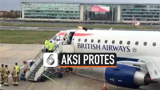 Seorang pengunjuk rasa berbaring di atas pesawat di Bandara London City. Ini merupakan bagian dari aksi protes terkait rencana pemerintah untuk memperluas bandara.