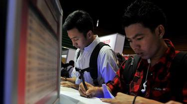Para pencari kerja rampak mengisi formulir lamaran di salah satu perusahaan peserta Career Expo (Liputan6.com/Johan Tallo)