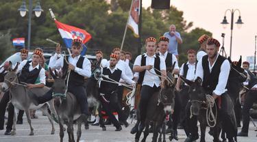 Para peserta berpartisipasi dalam kompetisi balap keledai tradisional ke-53 di Tribunj, Kroasia  (29/8/2020). (Xinhua/Pixsell/Hrvoje Jelavic)