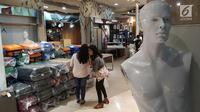 Calon pembeli melihat tumpukan tas koper yang dijual dengan potongan harga yang menggiurkan di Matahari Mall Taman Anggrek, Jakarta, Jumat (1/12). Matahari Department Store menawarkan diskon 20% hingga 70% jelang penutupan. (Liputan6.com/Fery Pradolo)