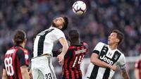 Gelandang Juventus, Emre Can, duel udara dengan gelandang AC Milan, Tiemoue Bakayoko, pada laga Serie A di Stadion Allianz, Turin, Sabtu (6/4). Juventus menang 2-1 atas AC Milan. (AP/Andrea Di Marco)