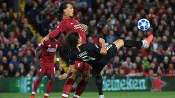 Striker PSG, Edinson Cavani, berebut bola dengan bek Liverpool, Virgil van Dijk, pada laga Liga Champions di Stadion Anfield, Liverpool, Selasa (18/9/2018). Liverpool menang 3-2 atas PSG. (AFP/ Paul Ellis)