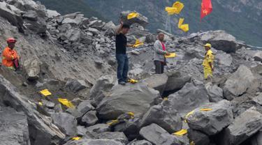 Keluarga korban melemparkan kertas ritual untuk menenangkan arwah orang yang tewas di lokasi tanah longsor di desa Xinmo, Sichuan, China (25/6). Sekitar 118 orang hilang diduga tertimbun bebatuan akibat longsor ditempat tersebut. (AP Photo / Ng Han Guan)