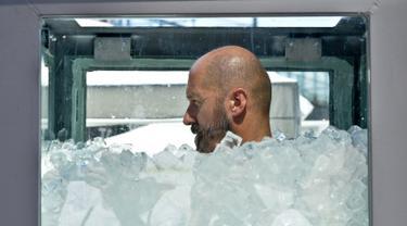 Atlet Austria, Josef Koeberl berupaya memecahkan rekor dengan berendam dalam kotak yang diisi tumpukan es batu di Wina, Sabtu (10/8/2019). Josef Koeberl berhasil memecahkan rekor dunia sebagai pria terlama yang mampu bertahan di dalam es selama 2 jam 8 menit 47 detik. (HERBERT NEUBAUER/APA/AFP)