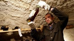 Pengurus kastil memeriksa botol anggur dari abad ke-19 yang disimpan dalam ruang bawah tanah di Kastil Becov di Becov nad Teplou, Republik Ceko, (22/5/2016).  (REUTERS/David W Cerny)