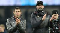 Pelatih Liverpool, Jurgen Klopp dan gelandang James Milner menyapa fans usai pertandingan melawan Manchester City pada lanjutan Liga Inggris di stadion Etihad (3/1). Kini Liverpool dan City hanya terpaut empat poin. (AP Photo/Jon Super)