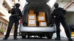 Polisi Thailand berjaga di mobil berisi 100 kilogram ganja sitaan sebelum konferensi pers di Bangkok, Selasa (25/9). Ganja itu akan diserahkan untuk penelitian medis menyusul rencana pemerintah memproduksi obat-obatan berbasis ganja. (AP/Sakchai Lalit)