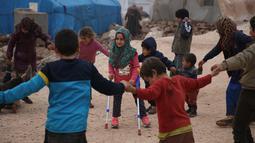 Bocah Suriah, Maya Merhi bermain bersama teman-temannya di kamp Serjilla, 9 Desember 2018. Sebelumnya, gadis 8 tahun yang lahir tanpa kaki karena kondisi bawaan terpaksa menggunakan kaki palsu dari kaleng ciptaan sang ayah. (Aaref WATAD/AFP)