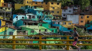 Seorang wanita berolahraga sambil menyusuri kawasan kumuh El Pesebre di pinggiran kota Medellin, Kolombia, 19 Juni 2017. Seniman Prancis, Tarik Bouanani melukis 230 rumah di kawasan tersebut membentuk mural raksasa. (JOAQUIN SARMIENTO/AFP)