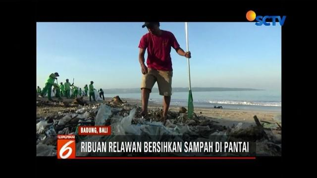 Jaga lingkungan agar para wisatawan senang, ribuan pelajar dan relawan membersihkan sampah di sepanjang Pantai Kedonganan hingga Kuta, Bali.