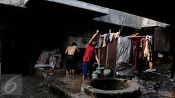 Warga mengambil air di sumur disamping tempat huniannya di kolong jembatan Penjagalan, Penjaringan, Jakarta, Kamis (13/8/2015). Mahalnya biaya hidup dan sewa layak di Jakarta membuat mereka terpaksa tinggal di kolong jembatan. (Liputan6.com/Johan Tallo)