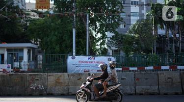 Pengendara motor melintas di sekitar perlintasan sebidang dekat Stasiun Palmerah dan Gedung DPR/MPR yang ditutup permanen di Jakarta, Selasa (1/12/2020). Perlintasan itu kini sudah ditutup permanen menggunakan barrier beton. (Liputan6.com/Immanuel Antonius)