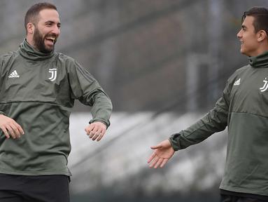 Penyerang Juventus, Gonzalo Higuain (kiri) dan Paulo Dybala tertawa saat latihan di pusat pelatihan Juventus di Vinovo (2/4). Juventus akan bertanding melawan Real Madrid pada leg pertama babak perempatfinal Liga Champions. (AFP Photo/Marco Bertorello)