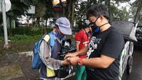Salah seorang pentolan VIking Persib Club Yana Umar membagikan masker dan sembako kepada warga yang membutuhkan. (Dok Viking Persib Club)