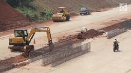 Aktivitas pekerja proyek pembangunan Tol Kunciran-Serpong di Jombang, Tangerang Selatan, Banten, Sabtu (24/11). Target pembangunan Tol Kunciran-Serpong molor akibat terkendala pembebasan lahan. (Liputan6.com/Angga Yuniar)