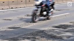 Pengendara motor melintasi jalan berlubang di Gunung Sahari, Jakarta, Selasa (29/1). Sedikitnya terdapat 8 titik jalan rusak dan berlubang di sepanjang Jalan Gunung Sahari berdiameter hingga 10 cm dengan kedalaman 10 cm. (Merdeka.com/Iqbal S. Nugroho)