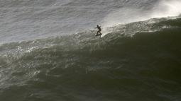 Seorang peselancar mengendarai papan hidrofoil menuruni gelombang selama sesi selancar derek di Praia do Norte atau Pantai Utara di Nazare, Portugal, Kamis (29/10/2020). (AP Photo/Pedro Rocha)