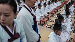 Sejumlah pelajar mengenakan kostum tradisional Korsel saat upacara Hari Kedewasaan di Namsan Hanok Village, Seoul, Senin (15/5). Di usia 20, mereka diperbolehkan merokok, mengonsumsi minuman beralkohol, dan mengikuti pemilihan umum. (Ed JONES/AFP)