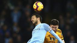Gelandang Manchester City, David Silva, duel udara dengan pemain Wolverhampton Wanderers, Matt Doherty, pada laga Premier League di Stadion Etihad, Manchester, Senin (14/1). Manchester City menang 3-0 atas Wolverhampton Wanderers. (AP/Dave Thompson)