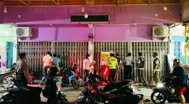Satgas Covid-19 di Riau membuka toko pakaian yang menutup pintu tapi ramai orang berbelanja di dalam.