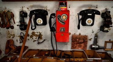 """Telepon tua dan barang antik lainnya dipajang di toko milik Manuel Mosquera di """"Pulgas' Market'' di Pamplona, Spanyol utara, (2/3). (AP Photo/Alvaro Barrientos)"""