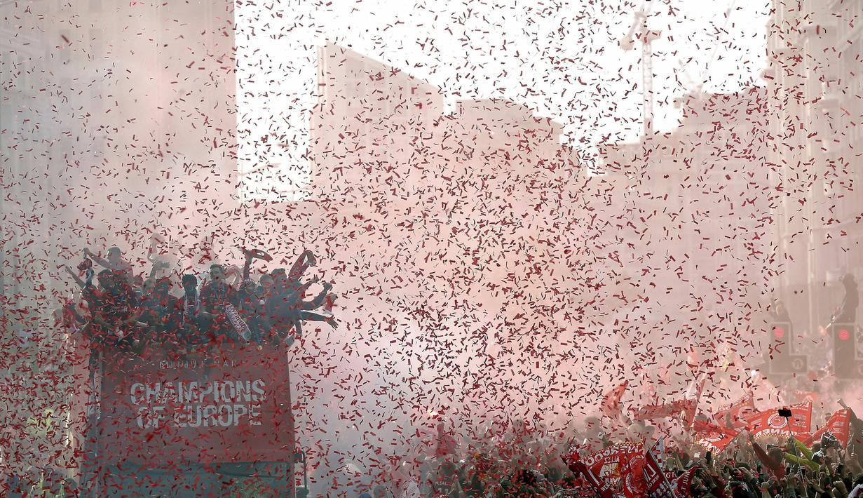 Para pemain Liverpool menyapa fans saat parade juara Liga Champions 2019 di Liverpool, Minggu (2/6). Ribuan fans tumpah ruah di jalanan untuk merayakan keberhasilan pemain membawa pulang trofi Si Kuping Besar ke kota Liverpool. (AP/Barrington Coombs)