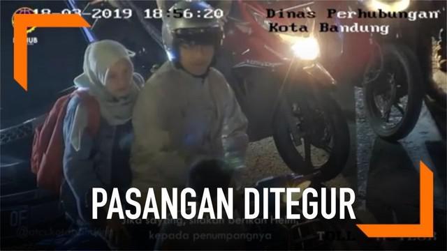Sebuah rekaman closed-circuit television (CCTV) memperlihatkan sepasang muda-mudi tengah berboncengan naik sepeda motor viral di media sosial lantaran melanggar lalu lintas.
