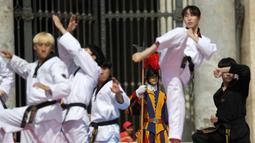 Atlet Taekwondo dari Korea Selatan melakukan gerakan saat tampil di depan Paus Fransiskus saat pertemuan umum mingguan di Lapangan Santo Petrus, Vatikan (30/5). (AP Photo/Gregorio Borgia)