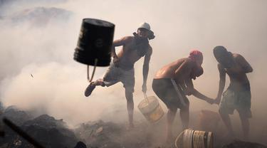 Warga berusaha memadamkan api dengan ember berisi air di Santa Ana, Asuncion, Paraguay, Kamis (19/8/2021). Api yang membakar kawasan pemukiman warga berpenghasilan rendah itu bermula dari orang-orang yang membakar sampah kemudian menjalar dan menghancurkan selusin rumah. (AP Photo/Jorge Saenz)